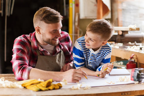 Father and son working together at a drafting table