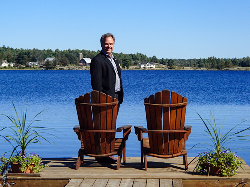 Eric Gonneau and two Muskoka chairs on a dock